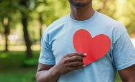 A volunteer holds a paper heart in front of his chest.