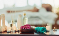 A woman relaxes at a spa. In the foregroun, a towel, candles and various other wellness items sit on a table.