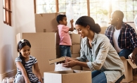 A family packs boxes, preparing for a move with kids.