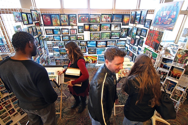Patrons browse a booth at the Plymouth Arts Fair.