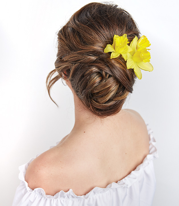 A woman with a yellow flower in her hair models a hairstyle from Christopher J Salon.