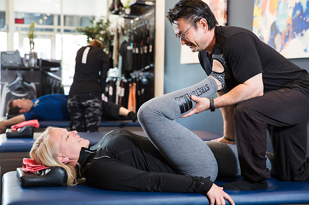 A Flexologist helps a woman with assisted stretching at StretchLab of Plymouth.