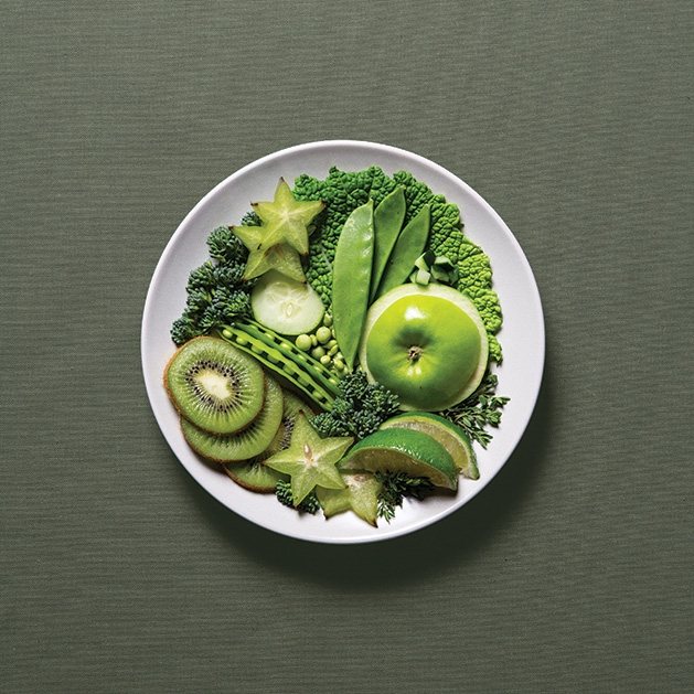 A plate full of healthy, green food options like kiwis, apples, peas, limes and more.