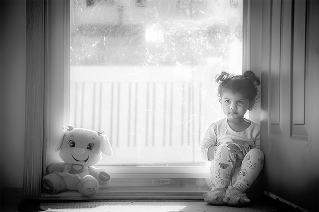 A girl sits six feet from her stuffed animal.