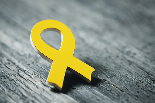 A yellow ribbon pin, signifying support for veterans.