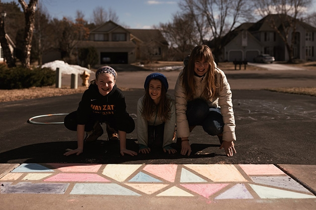 Ann Grocholski and her kids pose with their sidewalk chalk mural.