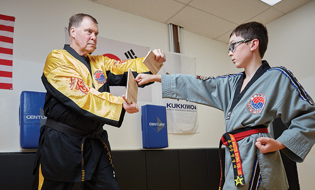 World Taekwondo Academy grand master Kevin Kastelle trains a child with special needs.