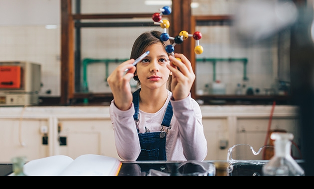 A girl performs an experiment at the Young Scientist Roundtable.