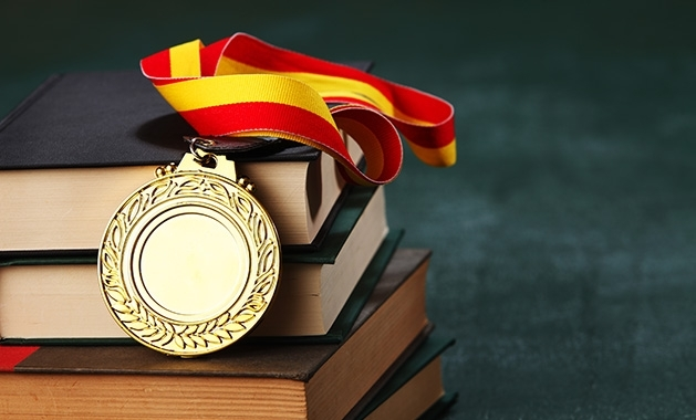 An educational award sits atop a pile of books.