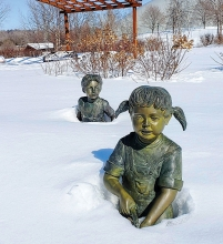 Boy and girl statues in Plymouth's Millennium Garden covered in snow.