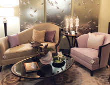 A living room remodeled by Jayne Morrison Interiors, featuring a tan sofa with purple and tan throw pillows, a purple chair, a glass top coffee table and many accent pieces.