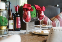 A holiday table spread featuring wine and wine glasses, candles, a place setting and more.