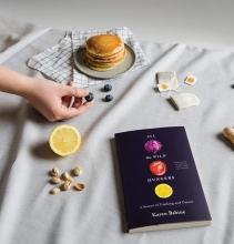 """A copy of """"All the Wild Hungers"""" by Karen Babine is surrounded by tea, pancakes and other fall foods."""