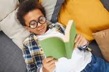 Boy reading book while laying down