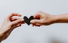 Someone hands a black paper heart to another person.